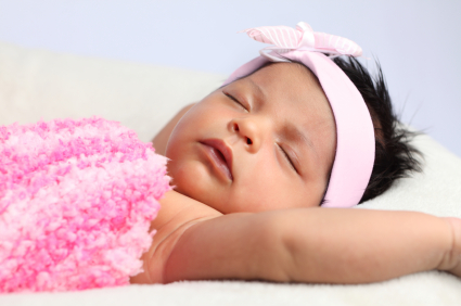a sleeping newborn baby wearing a pink bow